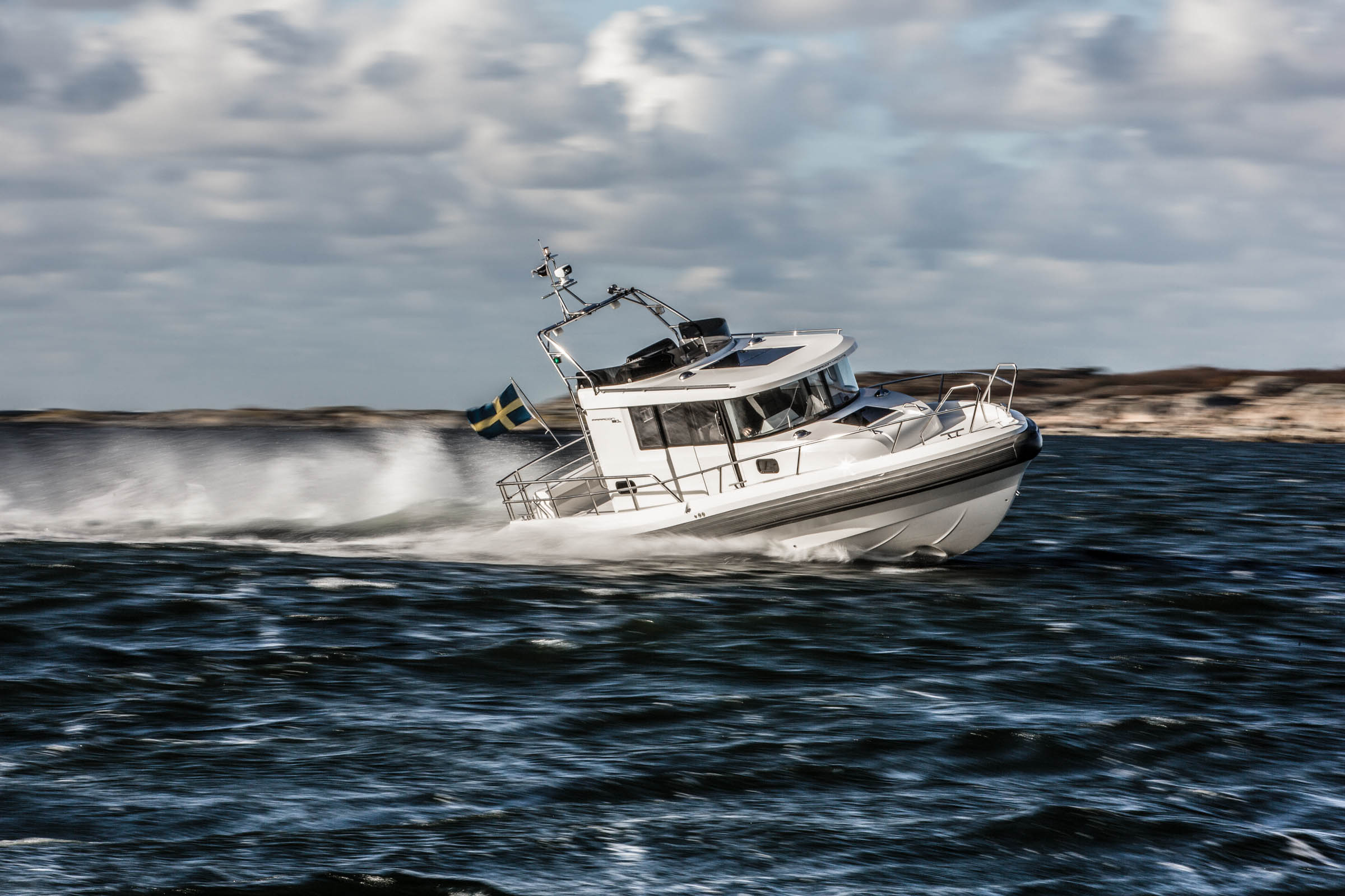 Paragon 31 driving fast on the water, close to the land or an island