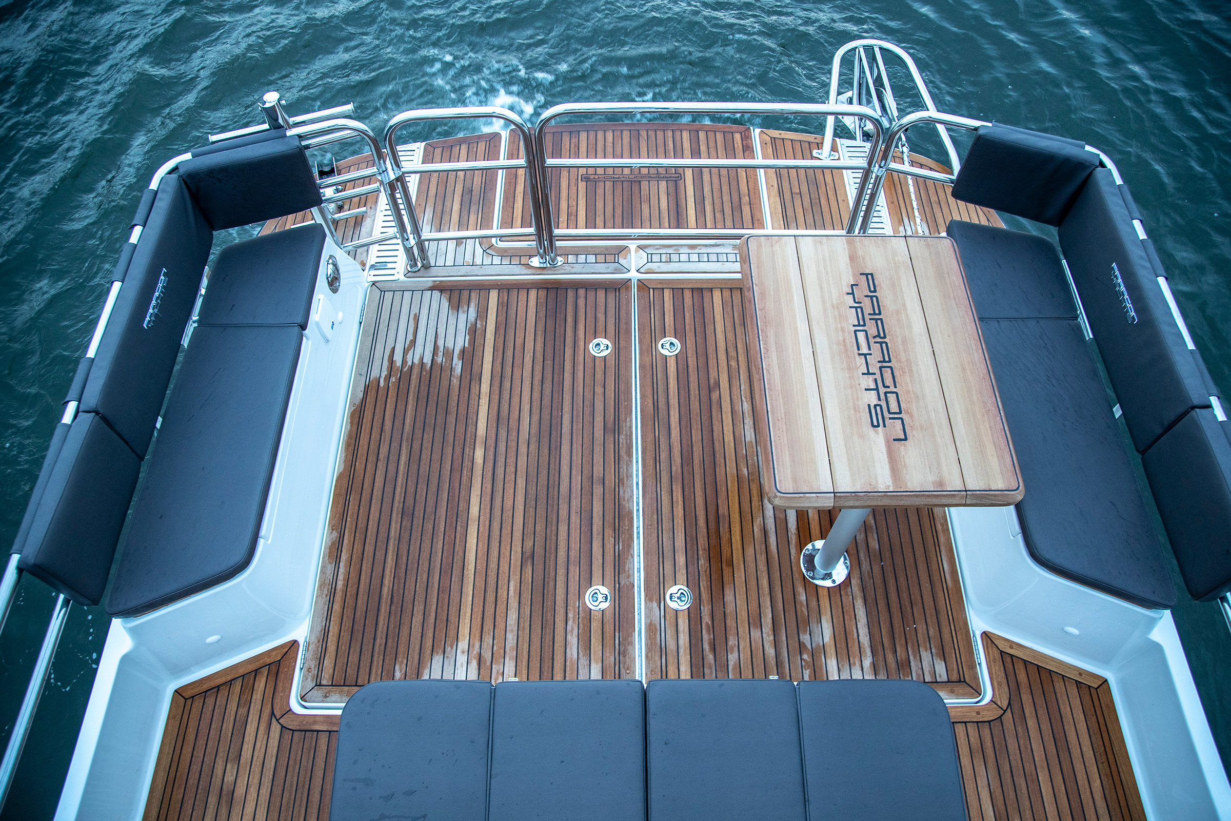 Back of a Paragon 31 Flybridge. A little lounge area with some sofas and a table